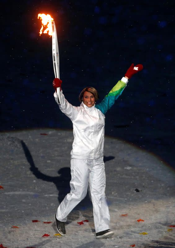 FILE PHOTO: Former Canadian speed skater Catriona Le May Doan carries the Olympic torches during the opening ceremony of the Vancouver Winter Olympic Games at the BC Place stadium in Vancouver