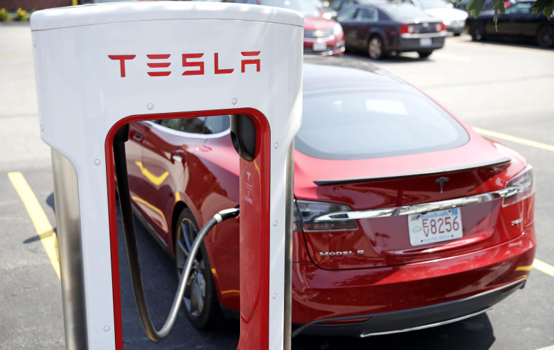 FILE- In this Aug. 24, 2018, file photo a Tesla Model S is plugged in at a vehicle Supercharging station in Seabrook, N.H. Shares of Tesla slipped on Monday, Aug. 27, the first day of trading after the electric vehicle maker said it won't consider going private after all. (AP Photo/Charles Krupa, File)
