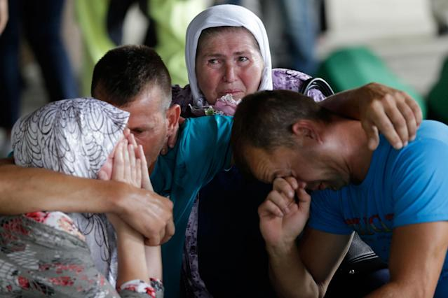 <p>People cry by the coffin of a relative, among 71 coffins displayed at the memorial centre of Potocari near Srebrenica, 150 kms north east of Sarajevo, in Bosnia, Sunday, July 9, 2017, where the newly identified victims of Europe's worst massacre since World War II will be buried on the 22th anniversary of the crime on Tuesday. (Photo: Amel Emric/AP) </p>