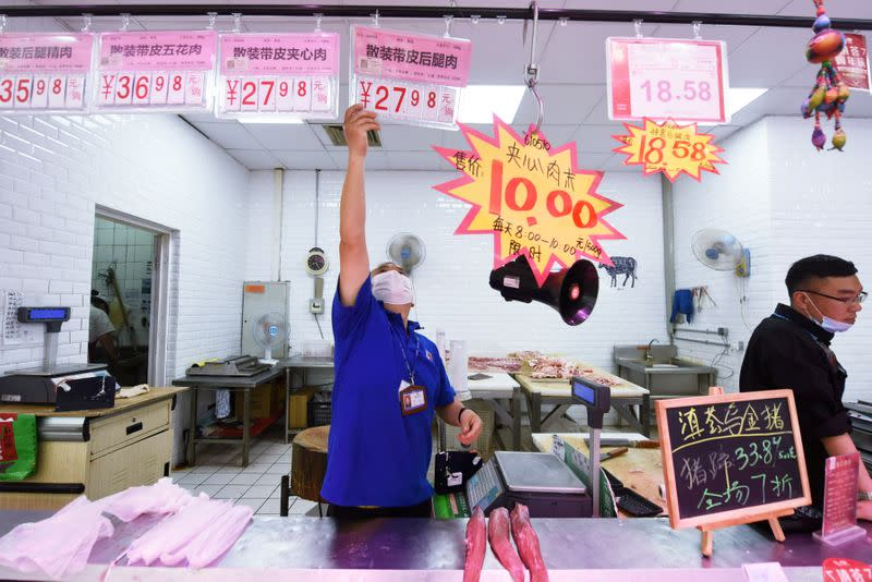 FILE PHOTO: Staff member puts up a price sign at a pork counter inside a supermarket in Hangzhou