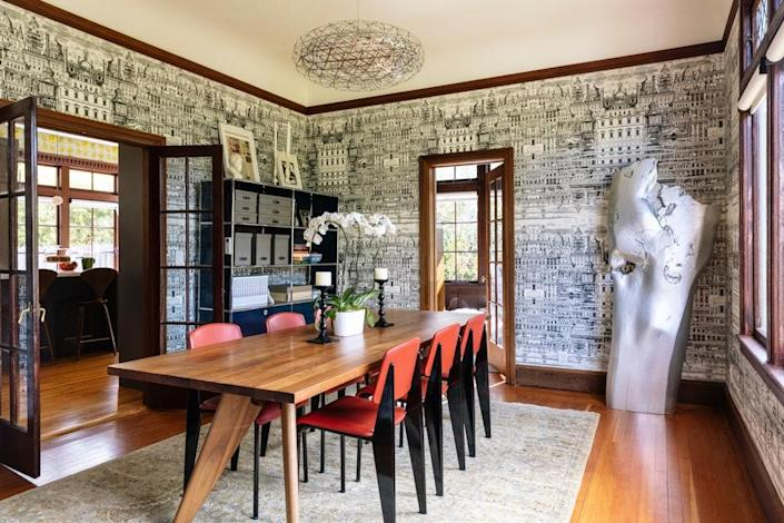 In another dining area, which is wrapped in Riflesso architectural wallpaper by Fornasetti, the dining chairs and table are all by Jean Prouvé for Vitra. The sculpture is by Nick De Pirro.