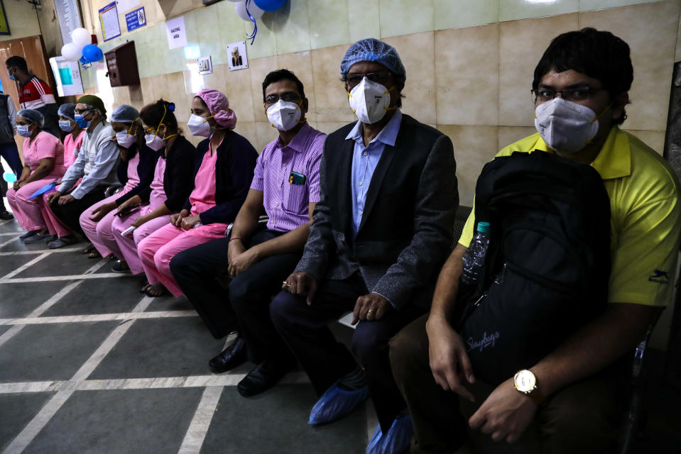 First batch of health workers wait for their turn to get vaccinated at a hospital in Kolkata, India, Saturday, Jan. 16, 2021. India started inoculating health workers Saturday in what is likely the world's largest COVID-19 vaccination campaign, joining the ranks of wealthier nations where the effort is already well underway. (AP Photo/Bikas Das)