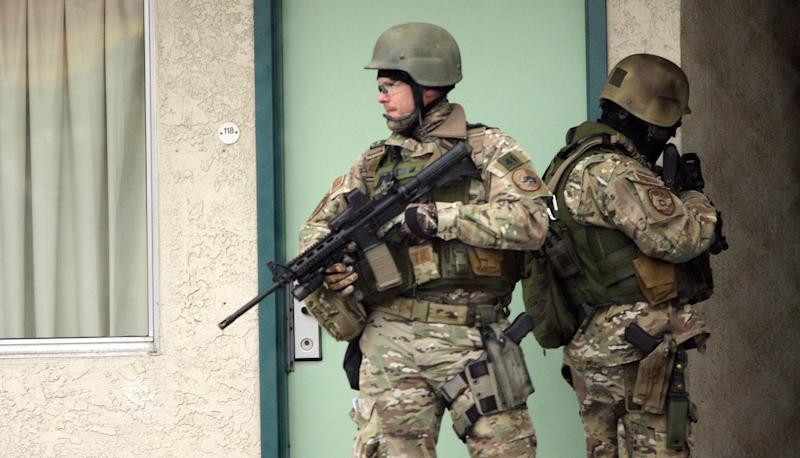 """Unified Police Department SWAT officers look for a person of interest at a local Midvale, Utah motel in connection with a multiple victim shooting, Tuesday, Feb. 12, 2013. Three people were shot to death and one was critically wounded at a known drug house in suburban Salt Lake City, causing temporary lockdowns at several area schools as police looked for two men who may have been involved. Investigators said a person inside the house reported the shooting in Midvale at about 8 a.m. Unified Police Department Lt. Justin Hoyal said a search warrant had been served at the house in recent weeks for drug activity. """"It was a known narcotics house,"""" he said. (AP Photo/The Deseret News, Jeffrey D. Allred)  SALT LAKE TRIBUNE OUT;  MAGS OUT"""