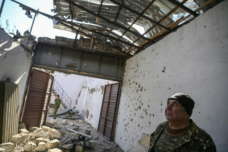 The mayor of Martakert Misha Gyurjian stands inside a building destroyed by shelling