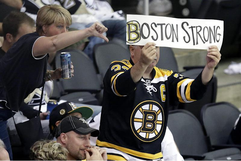 A Boston Bruins fan, right, holds a sign during the third inning in Game 1 of the NHL hockey Stanley Cup Eastern Conference finals between the Boston Bruins and Pittsburgh Penguins in Pittsburgh, Saturday, June 1, 2013. The Bruins won 3-0. (AP Photo/Gene J. Puskar)