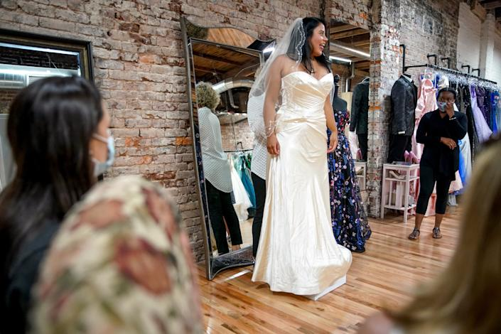 Marisol De La O, center, a paramedic from Nashville, exclaims at a dress she tries on with her friends to help her decide at Wedding Belles in Clarksville, Tenn., on Tuesday, Aug. 11, 2020.