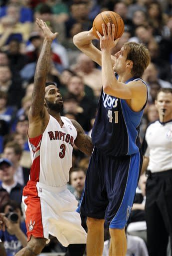 Dallas Mavericks forward Dirk Nowitzki (41) shoots the ball against Toronto Raptors forward Gary Forbes (3) during the first half of an NBA basketball game in Dallas on Friday Dec. 30, 2011. (AP Photo/Mike Fuentes)
