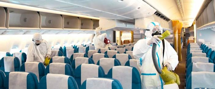Cleaners disinfecting the inside of an aircraft in full PPE