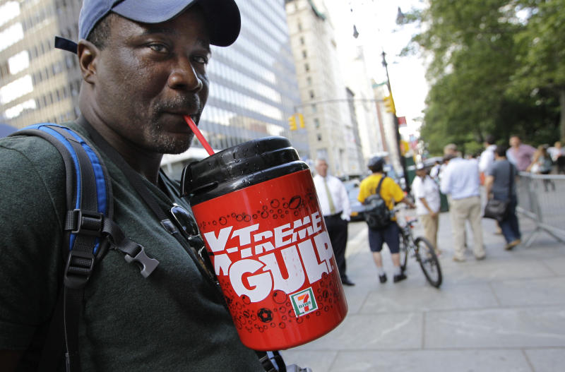 FILE - In this July 9, 2012 file photo, protester Eric Moore sips on an extra-large beverage during a protest against Mayor Michael Bloomberg's proposal to prohibit licensed food establishments from using containers larger than 16 ounces to serve high-calorie drinks at City Hall in New York. The era of the supersized cola may come to an end in New York City on Thursday, Sept. 13, 2012, when health officials are expected to approve the 16-ounce limit. (AP Photo/Kathy Willens, File)
