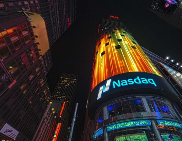 Nasdaq building in Times Square at night, with lights on the screen above the Nasdaq logo.
