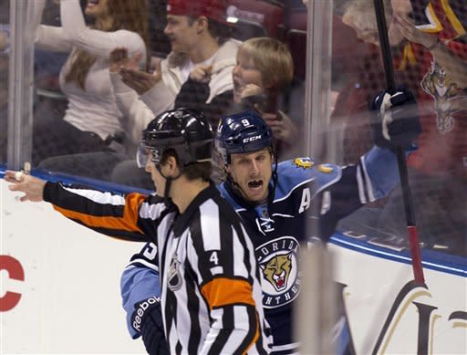 Florida Panthers' Stephen Weiss (9) celebrates teammate Tomas Fleischmann's goal as game official Wes McCauley (4) signals it was a good shot during the second period of an NHL hockey game against the Carolina Hurricanes in Sunrise, Fla., Sunday, March 11, 2012 against the Carolina Hurricanes. (AP Photo/J Pat Carter)