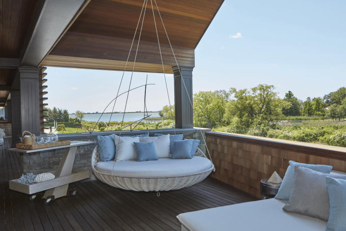 This image provided by Melanie Roy Design shows an outdoor swing lounger. Millions of people found themselves working from home during the past year. And many are likely to continue doing so this summer and beyond, even as pandemic restrictions ease. One bonus when working from home: spending some or all of your work day outside. (Anastassios Mentis/Melanie Roy Design via AP)