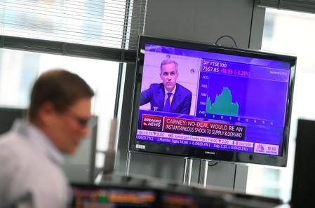 A television screen reporting financial news is seen whilst traders work at Northern Trust offices in London, Britain