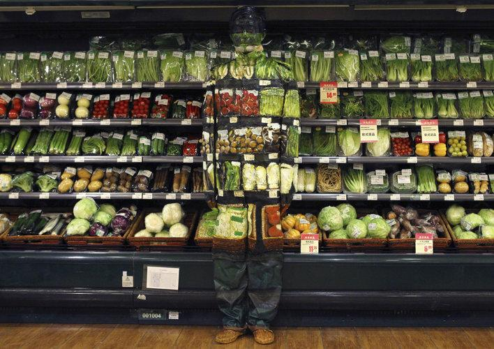 "Artist Liu Bolin demonstrates an art installation by blending in with vegetables displayed on the shelves at a supermarket in Beijing November 10, 2011. Liu, also known as the 'Vanishing Artist', started practising being ""invisible"" by means of optical illusions more than six years ago. Picture taken November 10, 2011."