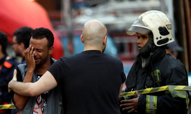<p>Firefighter officers comfort a man near the site where a building collapsed in downtown Sao Paulo, Brazil May 1, 2018. (Photo: Leonardo Benassatto/Reuters) </p>