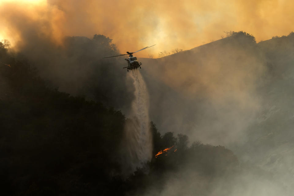 A firefighting helicopter drops water onto a brush fire scorching at least 100 acres in the Pacific Palisades area of Los Angeles on Saturday, May 15, 2021. (AP Photo/Ringo H.W. Chiu)