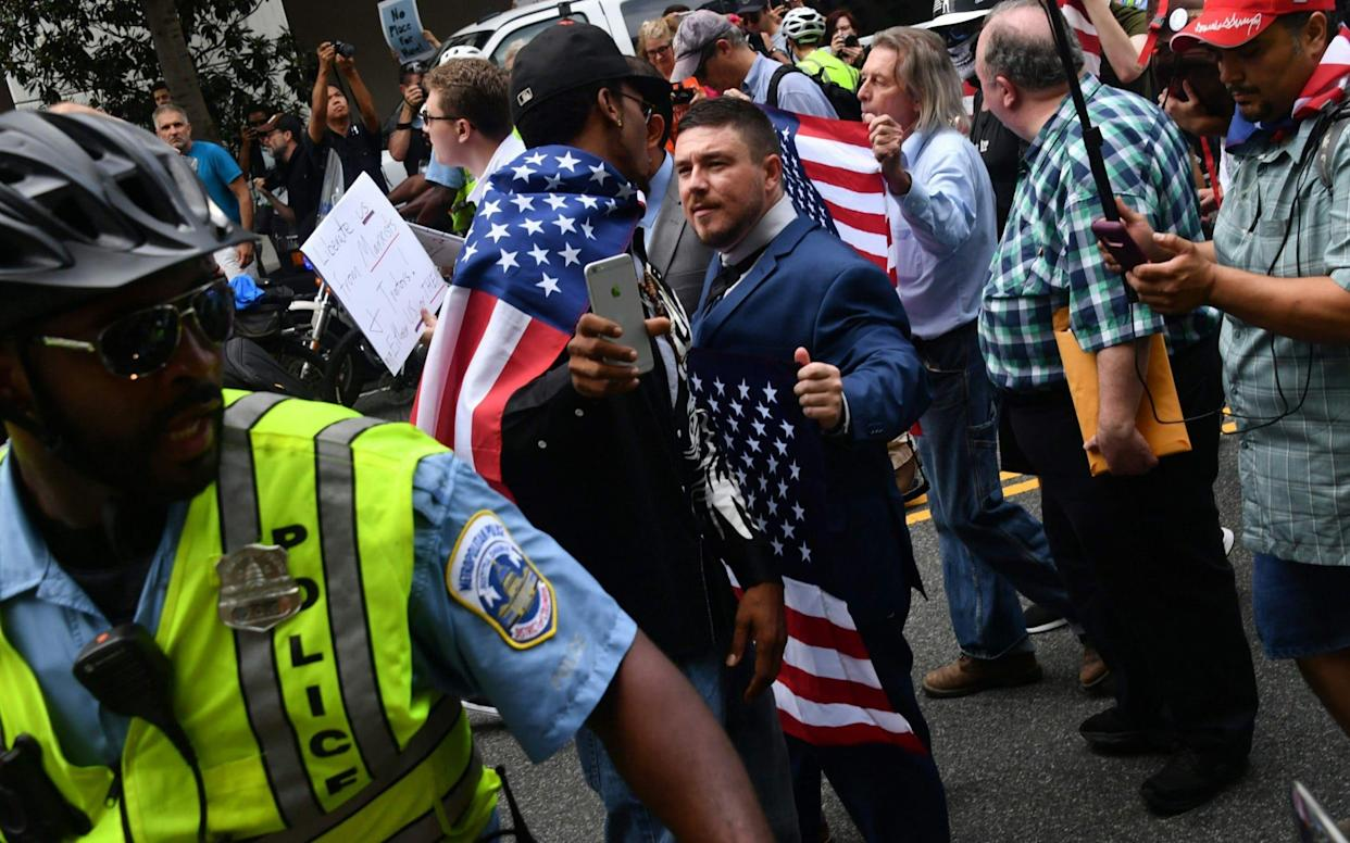 Jason Kessler, escorted by police during his August 12 rally outside the White House - AFP