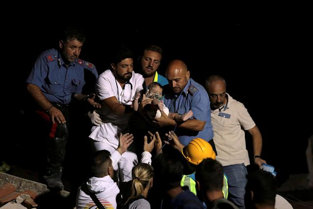 <p>Italian Carabinieri police officer and a doctor carry a child after an earthquake hit the island of Ischia, off the coast of Naples, Italy, Aug. 22, 2017. (Photo: Antonio Dilaurenzo/Reuters) </p>