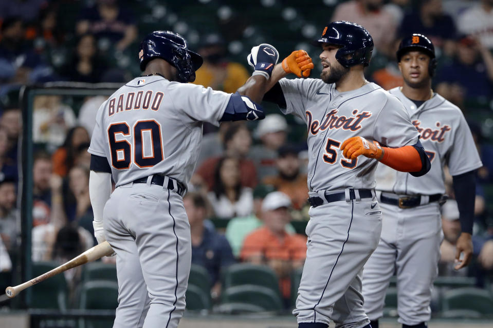 Detroit Tigers' Akil Baddoo (60) and Renato Nunez (55) celebrate Nunez's two-run home run as Jonathan Schoop, right, looks on during the fourth inning of the team's baseball game against the Houston Astros on Tuesday, April 13, 2021, in Houston. (AP Photo/Michael Wyke)