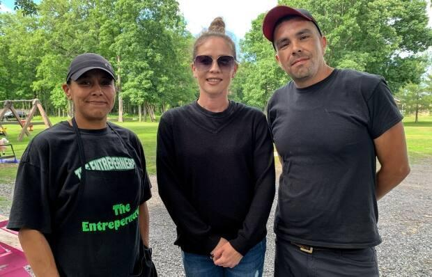 From left to right, Loriann Leaf, Colleen Lazore and Bronson Leaf are pictured outside their family business and home in Akwesasne. (Ahmar Khan/CBC News - image credit)
