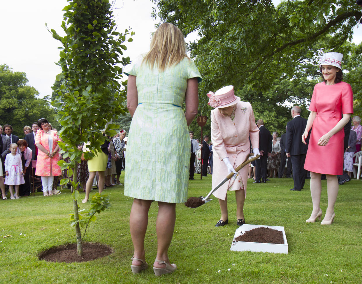 Britain's Queen Elizabeth plants a tree during a garden party at Hillsborough Castle, June 24, 2014. REUTERS/Liam McBurney/Pool (NORTHERN IRELAND - Tags: POLITICS ROYALS SOCIETY)