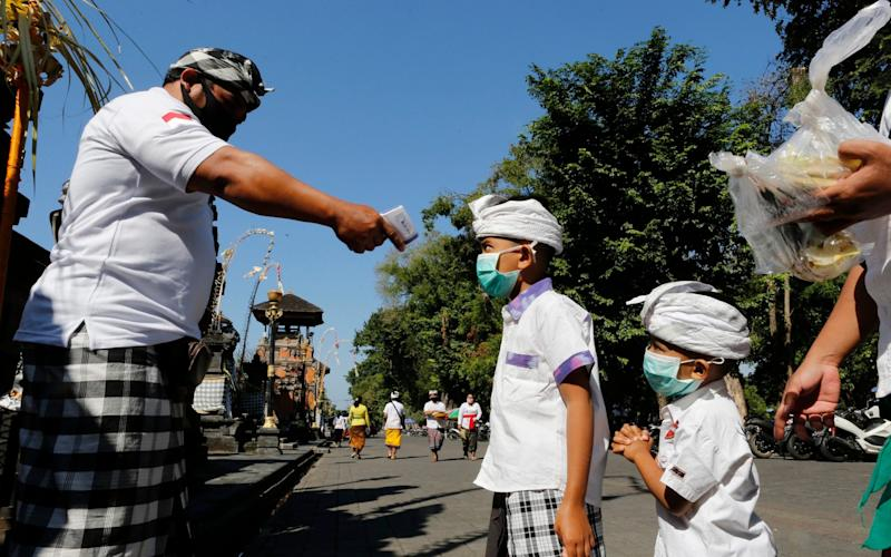 A security guard checks the body temperature of children at a temple  - AP