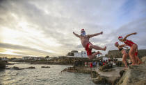 People take part in the annual Christmas Day swim at the Forty Foot bathing spot in Sandycove Dublin, Ireland, Friday Dec. 25, 2020. (Damien Storan/PA via AP)