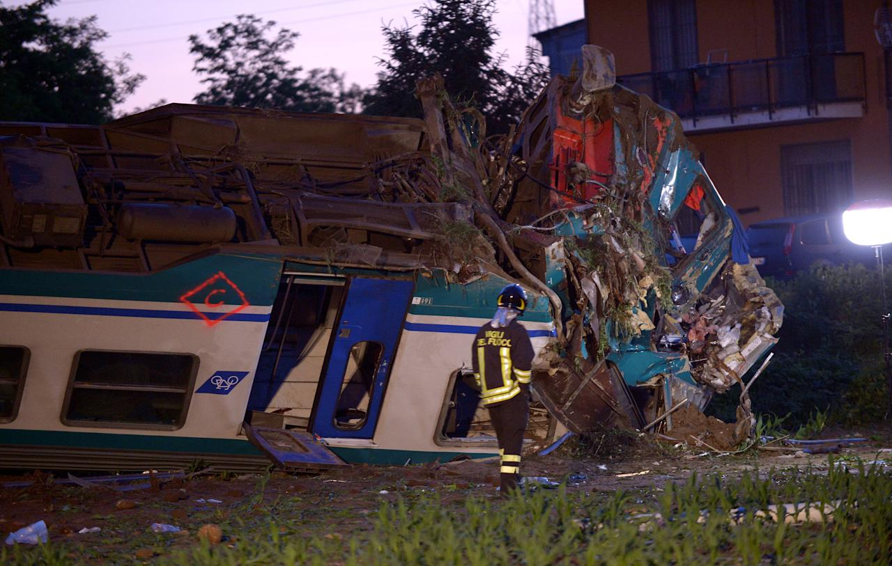 Fire fighter stand next to the twisted wreckage of a train that plowed into a truck last night in Caluso near Turin, Italy, May 24, 2018.  REUTERS/Massimo Pinca