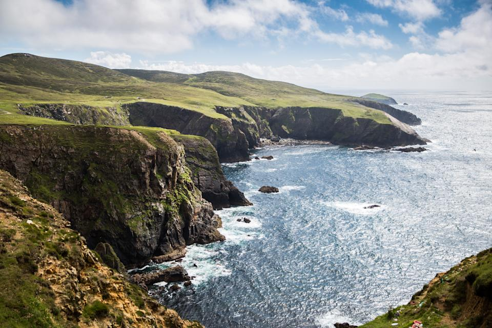 Up by the lighthouse on Arranmore Island, the 150 foot cliffs dominate the skyline with sea birds and rolling waves. Source: Getty
