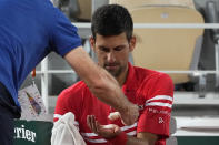 Serbia's Novak Djokovic gets some cream in his hand during a break as he plays Italy's Matteo Berrettini in a quarterfinal match of the French Open tennis tournament at the Roland Garros stadium Wednesday, June 9, 2021 in Paris. (AP Photo/Michel Euler)