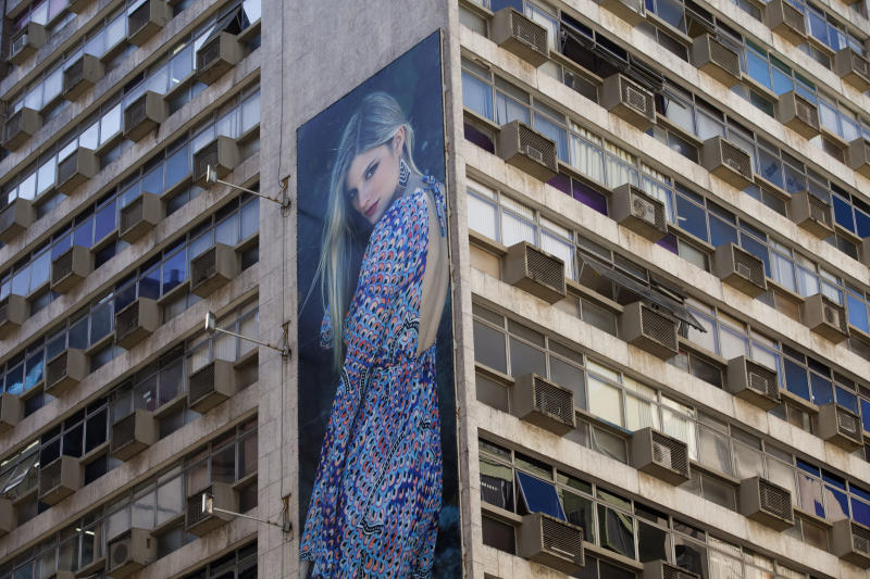 """A giant billboard advertising clothing is displayed on an office building in Rio de Janeiro, Brazil, Wednesday, May 2, 2012. Billboards on beachfront buildings, advertising along roadways and soccer fields, will now be torn down under the """"Clean Rio"""" campaign, meant to beautify the town before the 2014 World Cup and 2016 Olympics. (AP Photo/Victor R. Caivano)"""