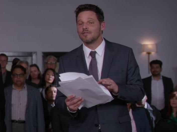 Alex Karev on Greys Anatomy holding papers and wearing a suit