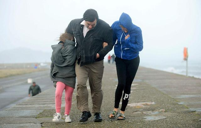 <p>A family walks along a seawall during storm Ophelia on East Pier in Howth, Dublin, Ireland, as the remnants of Hurricane Ophelia batter Ireland and the United Kingdom with gusts of up to 80mph (129kph), Monday Oct. 16, 2017. (Photo: Caroline Quinn/PA via AP) </p>