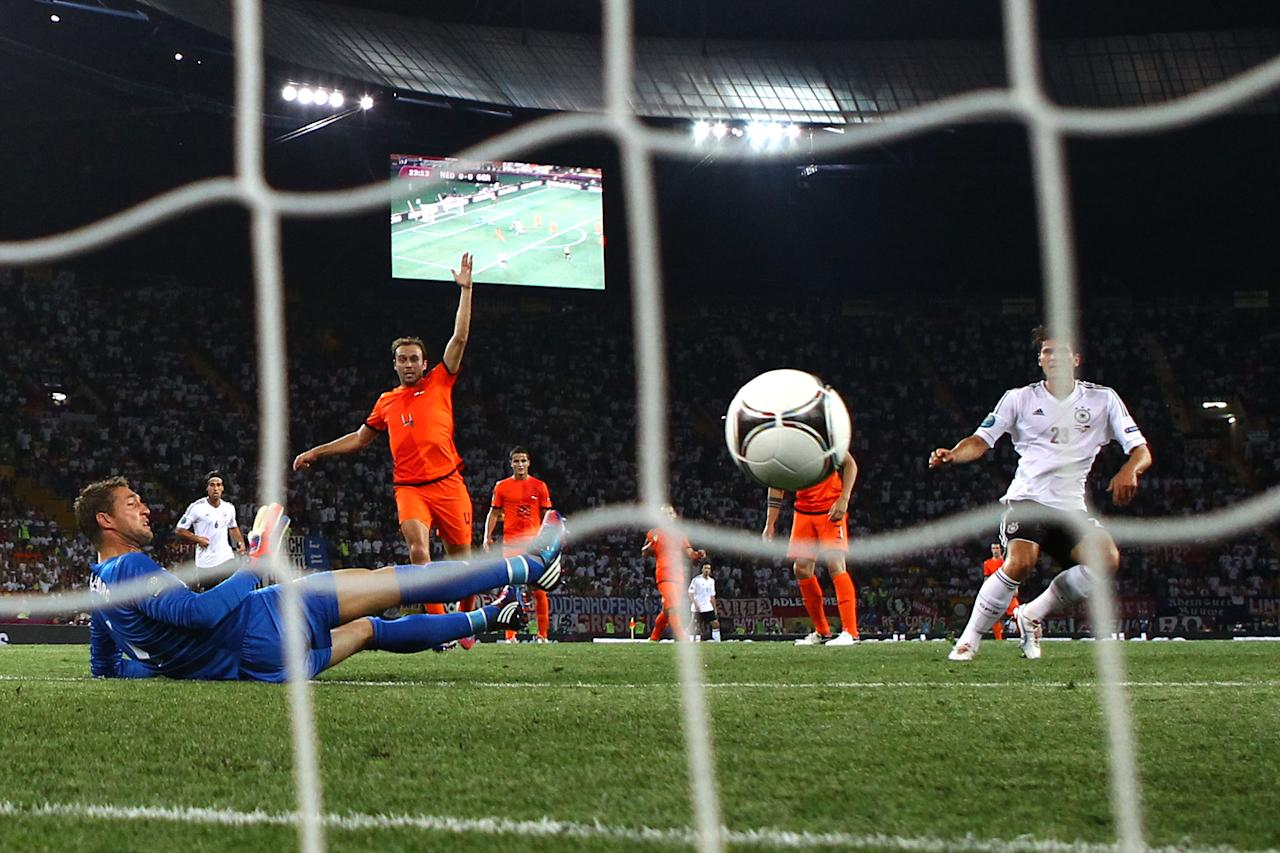 KHARKOV, UKRAINE - JUNE 13:  Mario Gomez of Germany scores their first goal past Maarten Stekelenburg of Netherlands during the UEFA EURO 2012 group B match between Netherlands and Germany at Metalist Stadium on June 13, 2012 in Kharkov, Ukraine.  (Photo by Julian Finney/Getty Images)