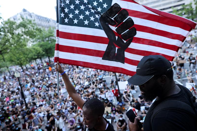 An American flag with a black fist is displayed to a crowd gathered in Washington, DC on June 6. Source: Getty Images