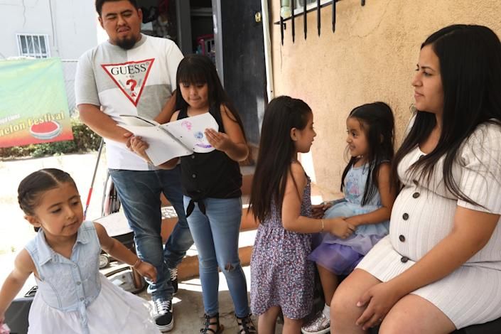 "Maria Reyes, right, and her husband Moises Bahena, watch over their daughters Leilani, 5, from left, Marilyn, 9, Sophia, 6, and Darlene, 4, at their home in Los Angeles on July 27. <span class=""copyright"">(Genaro Molina / Los Angeles Times)</span>"