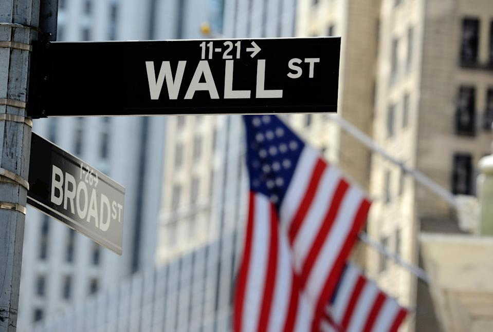 Wall St. street sign with American flags in the background
