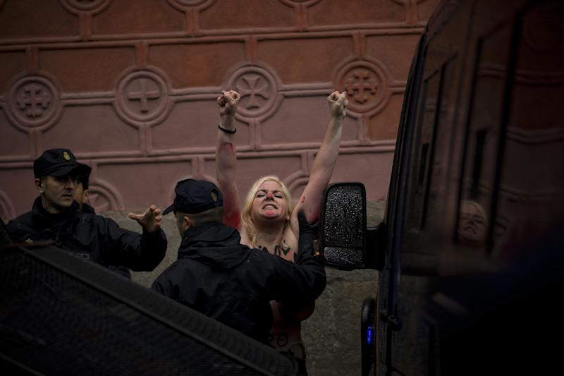 An activist from the women's movement Femen is dragged away by a police officer while they protest near a demonstration against the abortion in Madrid, Spain, Sunday, Oct. 17, 2013. The activists from the European feminist group were demonstrating with 'Abortion is Sacred', and 'keep out of my body' written on their bodies against the government's conservative new abortion law. (AP Photo/Daniel Ochoa de Olza)
