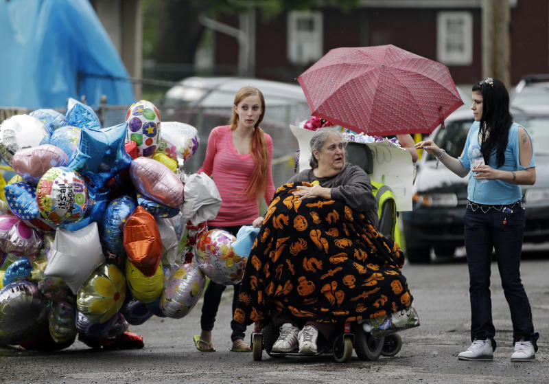FILE - In this May 10, 2013 file photo, Deborah Knight, center, grandmother of Michelle Knight, drives her wheelchair past the home of Gina DeJesus in Cleveland. Ariel Castro, 53, serving a life sentence for the kidnapping and rape of Knight and two other women, was found hanging in his cell, Tuesday night, Sept. 3, 2013, at the Correctional Reception Center in Orient, Ohio. (AP Photo/Mark Duncan, File)