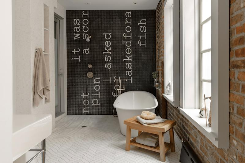 """Bathrooms are big in Tierney's home, both spatially and impact-wise. The master bath—a wet room outfitted in Calcutta marble—features a wall size mosaic inscribed by the artist Jennifer Seastone with the words It was not a scorpion I asked for I asked for a fish. It is the first line of Tierney's favorite poem """"Closing Time;Iskandariya"""" by Brigit Pegeen Kelly, which she came across years ago and was immediately transfixed by. """"I thought it would be nice to wake up to it every morning,"""" she says. The rosary beads are from the Vatican. """"I'm not religious, but I like Catholic iconography,"""" she explains."""