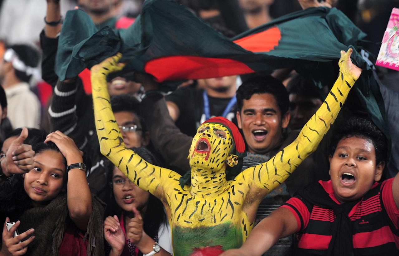 Bangladeshi cricket spectators celebrate as the Bangladesh cricket team won the series during the fifth one day international between Bangladesh and West Indies at The Sher-e-Bangla National Cricket Stadium in Dhaka on December 8, 2012. A spirited Bangladesh led by all-rounder Mohammad Mamhmudullah edged out the West Indies in the fifth and final one-day by two wickets in Dhaka, taking the series 3-2.     TOPSHOTS/AFP PHOTO/Munir uz ZAMAN