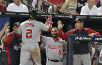 Washington Nationals' Denard Span (2) is greeted at the dugout by Danny Espinosa (8) and manager Davey Johnson, right, after scoring from third on a Ryan Zimmerman fly ball in the sixth inning of a baseball game against the Atlanta Braves in Atlanta, Friday, May 31, 2013. (AP Photo/John Bazemore)