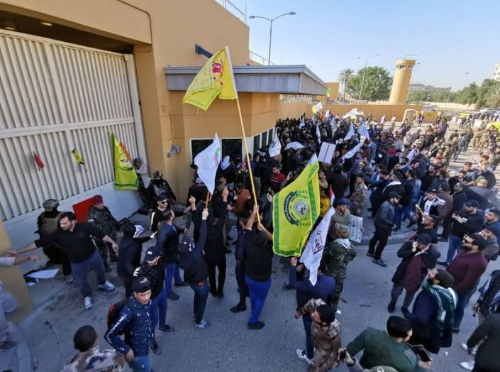 Protesters and militia fighters gather to condemn air strikes on bases belonging to Hashd al-Shaabi, outside the main gate of the U.S. Embassy in Baghdad