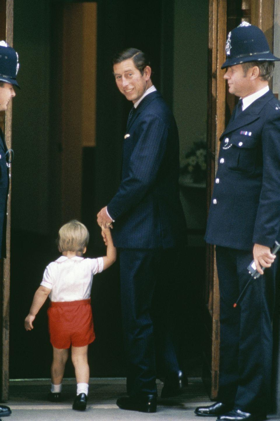 <p>Charles holds William's hand as they arrive at St Mary's Hospital to visit Princess Diana and newborn Prince Harry. </p>