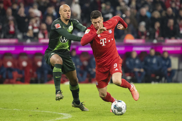 Bayern's Robert Lewandowski, right, and Wolfsburg's Marcel Tisserand battle for the ball during the Germany Bundesliga soccer match between Bayern Munich and VfL Wolfsburg at the Allianz Arena in Munich, Germany, Saturday, Dec. 21, 2019. (Matthias Balk/dpa via AP)