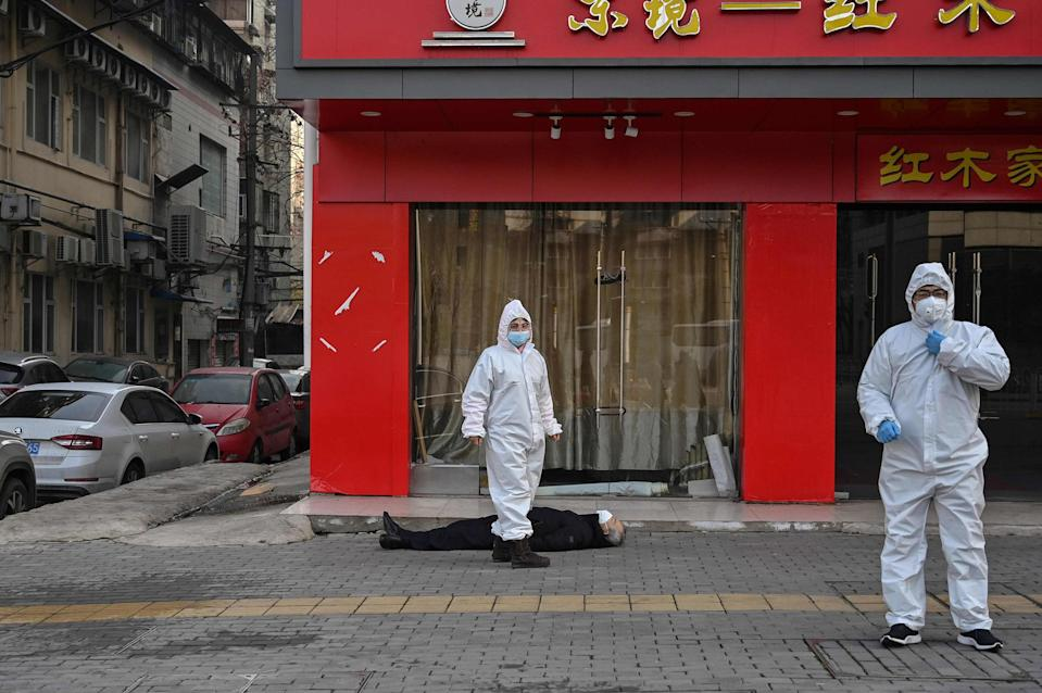 Image: Officials in protective suits checking on an elderly man wearing a facemask who collapsed and died on a street near a hospital in Wuhan