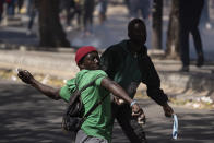 A demonstrators throws rocks at riot policemen during protests against the arrest of opposition leader and former presidential candidate Ousmane Sonko, Senegal, Monday, March 8, 2021. Senegalese authorities have freed opposition leader Ousmane Sonko while he awaits trial on charges of rape and making death threats. The case already has sparked deadly protests threatening to erode Senegal's reputation as one of West Africa's most stable democracies. That's because Sonko's supporters are accusing President Macky Sall of pursuing the criminal charges to derail the opposition figure's prospects in the upcoming 2024 election. (AP Photo/Leo Correa)