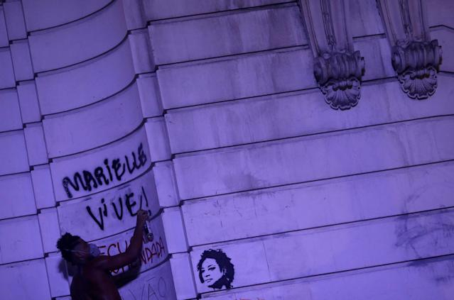 """A demonstrator graffitis """"Marielle lives!"""" as he takes part in a rally against the shooting of Rio de Janeiro city councilor Marielle Franco in Rio de Janeiro, Brazil March 16, 2018. REUTERS/Ricardo Moraes TPX IMAGES OF THE DAY"""