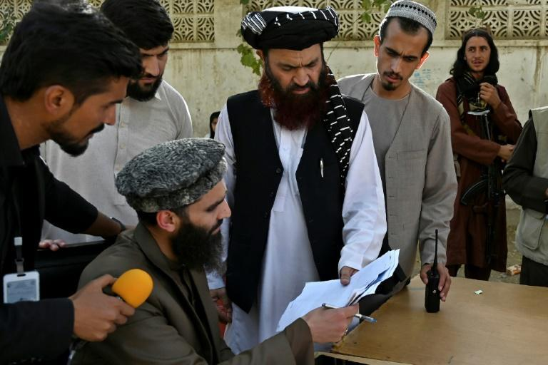 Mualvi Alam Gull Haqqani (C), head of the passport office, checks documents after the Taliban announced its reopening (AFP/WAKIL KOHSAR)