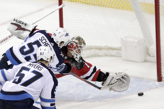 New Jersey Devils goaltender Keith Kinkaid, right, is unable to stop a shot by Winnipeg Jets center Mark Scheifele (55) during overtime of an NHL hockey game, Saturday, Dec. 1, 2018, in Newark, N.J. (AP Photo/Julio Cortez)